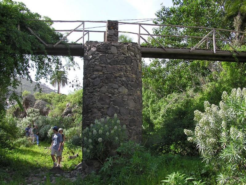 Hikers under a stone and wooden bridge